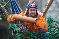 Dan Hooper, widely known as Swampy during the 1990s, holds a lock-on arm tube in a basket suspended from a bamboo tripod positioned in the river Colne on 8th December 2020 in Denham, United Kingdom. The climate and roads activist had occupied the tripod the previous day in order to delay the building of a bridge as part of works for the controversial HS2 high-speed rail link and a large security operation involving officers from at least three police forces, National Eviction Team enforcement agents and HS2 security guards was put in place to facilitate his removal.