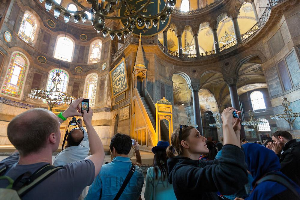 Tourists at Hagia Sophia, Ayasofya Muzesi, mosque museum using smartphones to take photographs in Istanbul, Republic of Turkey
