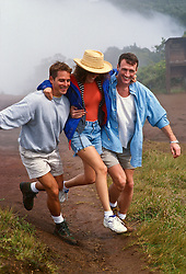 Two men and a woman walking playfully in Hawaii