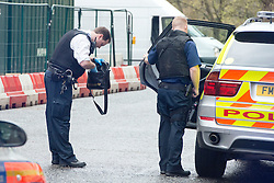 © Licensed to London News Pictures. 07/04/2014. London, UK. A police officer searches a bag. Armed Police arrest a man in King Charles Street today 7th April 2014. The street that runs between the Foreign Office and The Treasury, including an entrance to Downing Street has a search point at it's entrance. The man was led away to a waiting police van and officers were seen collecting evidence and an Adidas bag. . Photo credit : Stephen Simpson/LNP