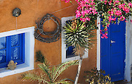 House painted orange with blue shutters in Greece.