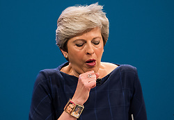 © Licensed to London News Pictures. 04/10/2017. Manchester, UK. British prime minister THERESA MAY attempts to clear he throat while delivering her leaders speech on the final day of the Conservative Party Conference. The four day event is expected to focus heavily on Brexit, with the British prime minister hoping to dampen rumours of a leadership challenge. Photo credit: Ben Cawthra/LNP