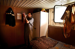 Third Engineer Mohamed Ali Gemal prays in his room between shifts while traveling between Egypt and Lebanon in the Mediterranean Sea on April 10, 2008. The Bisanzio, a feeder ship taking containers from Port Said to Beirut, is Lebanese owned, has three different nationalities aboard, and flies a St. Vincent flag. More than four religions are also represented on board.