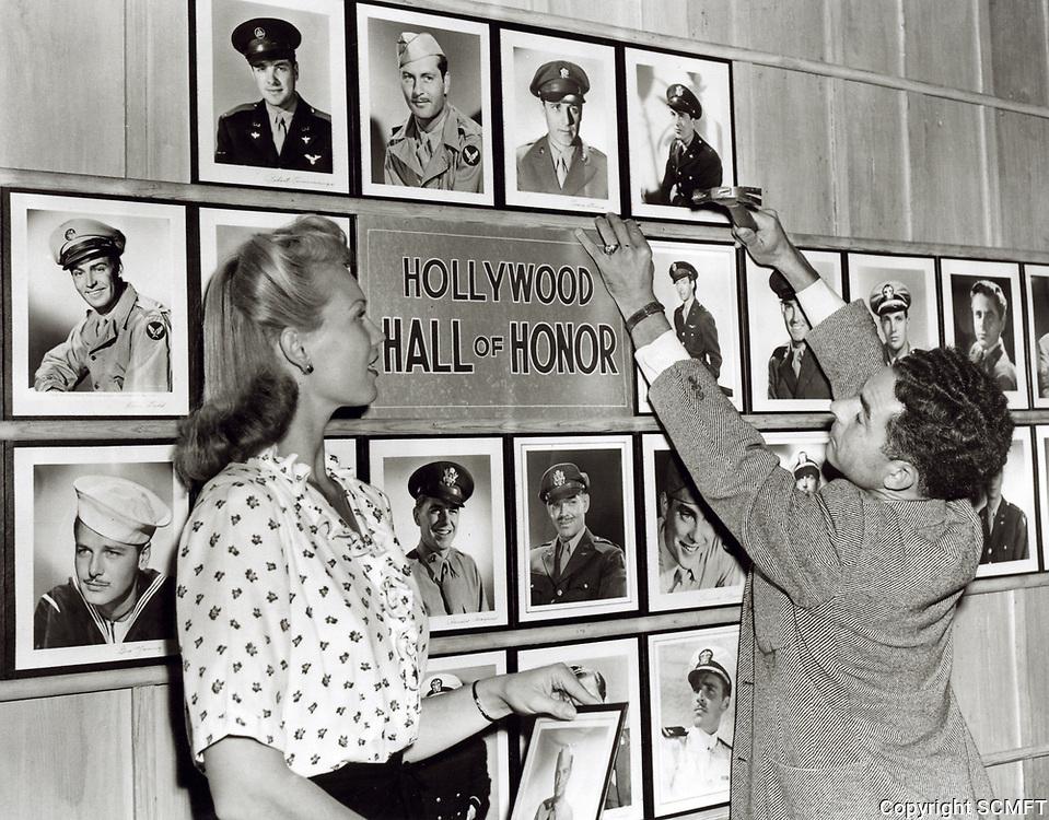 1943 Beautiful Bunny Waters Green helps Al Ybarra hang photos on the Hollywood Canteen's Hall of Honor