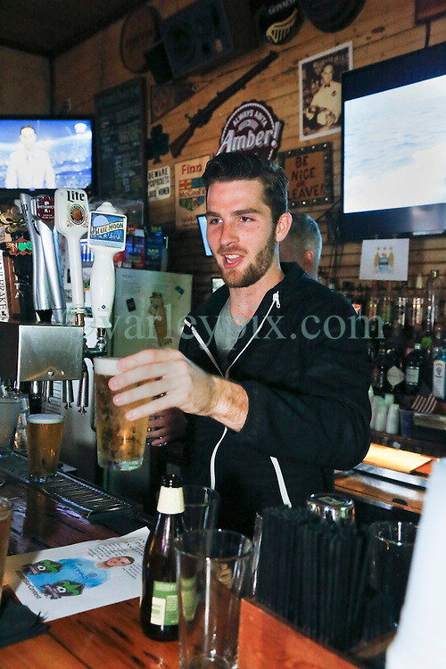 23 November 2015. Finn McCool's Irish Pub, New Orleans, Louisiana.<br /> Major League Soccer (MLS) star player Patrick Mullins of New York City FC serves a few pints to customers from behind the bar.<br /> Photo©; Charlie Varley/varleypix.com