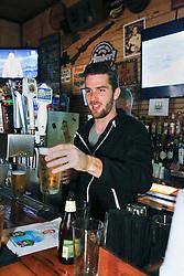 23 November 2015. Finn McCool's Irish Pub, New Orleans, Louisiana.<br /> Major League Soccer (MLS) star player Patrick Mullins of New York City FC serves a few pints to customers from behind the bar.<br /> Photo©; Charlie Varley/varleypix.com
