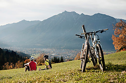 Two Mountainbikers resting on grass enjoying view
