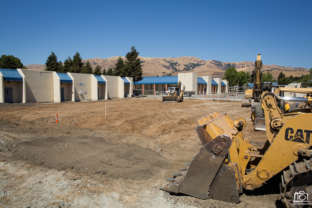 The old Milpitas High School swimming pools near the locker rooms have been covered with synthetic dirt to ensure load-bearing capabilities for future building projects, photographed at Milpitas High School in Milpitas, California, on July 18, 2014. (Stan Olszewski/SOSKIphoto)