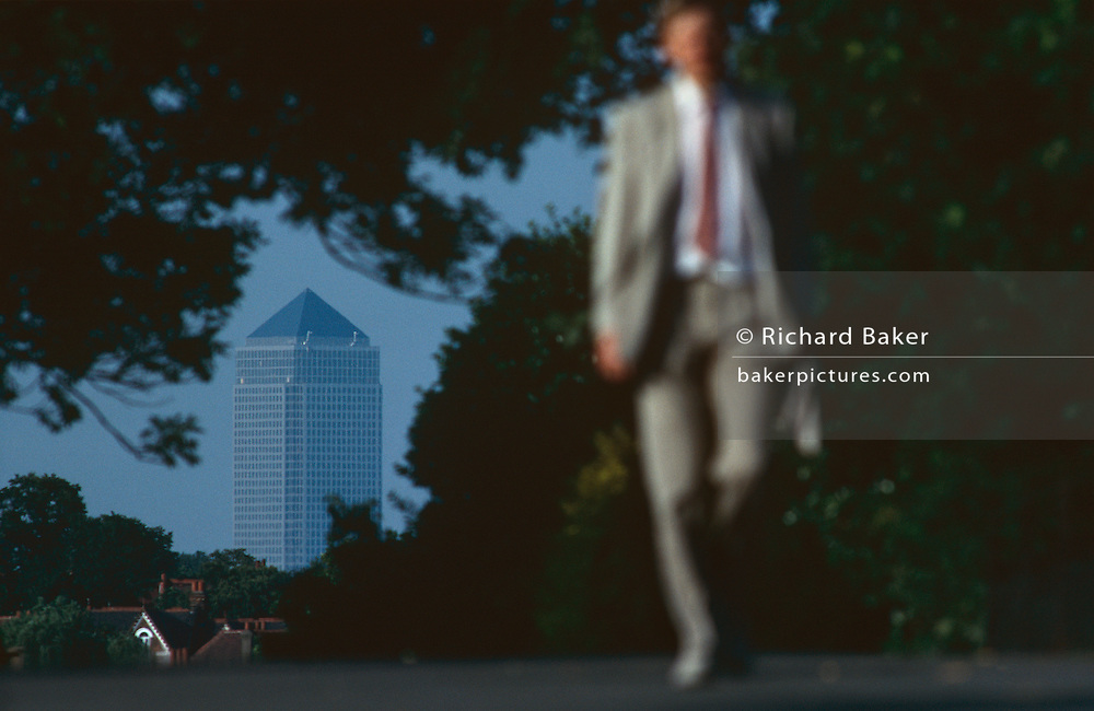 A businessman wearing a light summer suit and carrying a briefcase walks away in the opposite direction to Canary Wharf tower which is seen over his shoulder from across a tree-lined Brockwell Park in South London, approximately 7.5 miles away. The flattened-perspective is because of an extremely long telephoto lens making it seem closer than it is in reality. Canary Wharf is the product of the 1980s financial boom when during the office of Prime Minister Margaret Thatcher, huge building projects such as the Docklands consortium saw vast changes in London's landscape.