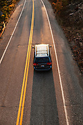 Car traveling along a road at sunset, Maine, USA