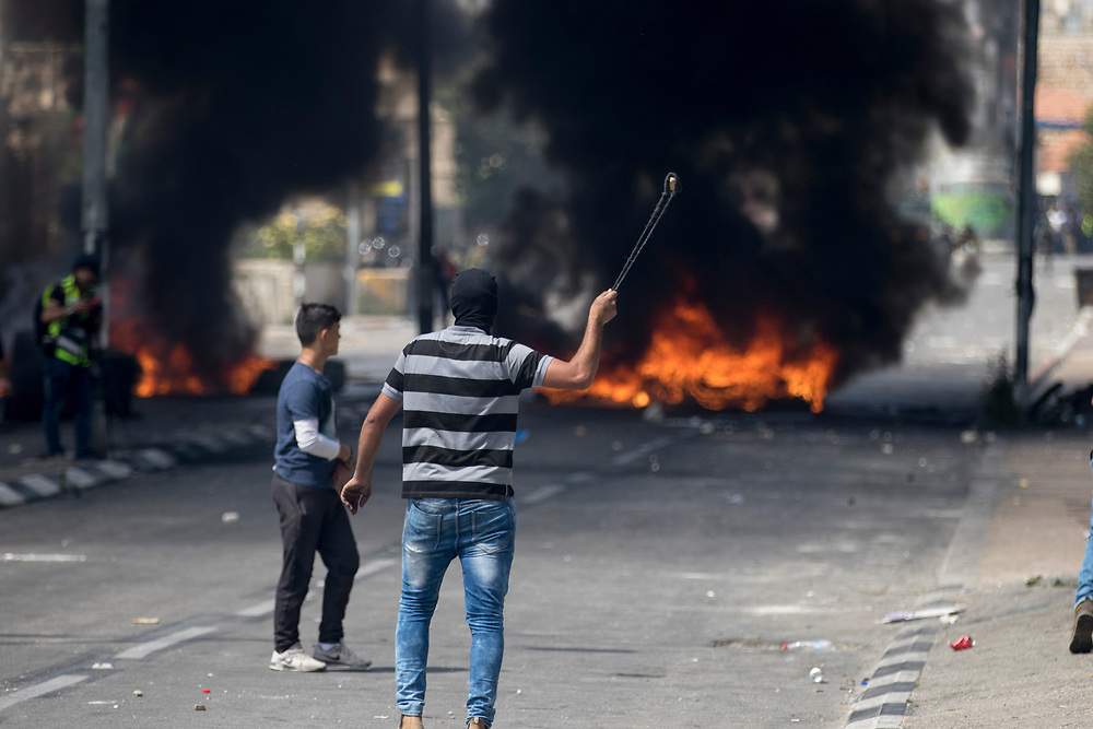 Bethlehem, Palestine. 15 May 2018. A protester uses a slingshot to fire rocks at Israeli soldiers on the 70th anniversary of the Nakba (Catastrophe) when over 700,000 Palestinians were forcibly moved from their homes during the creation of Israel. © Craig Redmond
