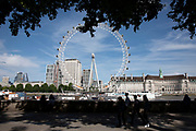 Tourists walk in silhouette across the river from the London Eye, one of the most famous landmarks, skylines and iconic buildings in the capital in London, England, United Kingdom. London Eye, also known as the Millennium Wheel.