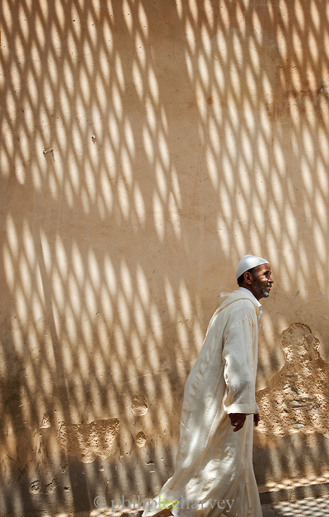 A man walking through the narrow streets of the medina after prayer, Fes, Morocco
