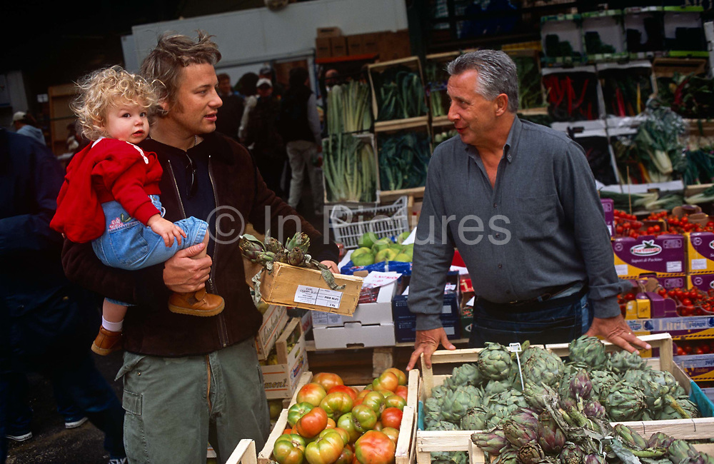 """TV chef Jamie Oliver shops for produce with a favoured veg seller in Borough Market in Southwark, London. Oliver holds his box of fresh artichokes in one hand an his very young daughter Poppy on a Saturday morning. James """"Jamie"""" Oliver, MBE (born 27 May 1975) is a British chef, restaurateur and media personality, known for his food-focused television shows, cookbooks and more recently his campaign against the use of processed foods in national schools. He strives to improve unhealthy diets and poor cooking habits in the United Kingdom and the United States."""
