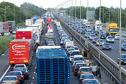 © Licensed to London News Pictures. 22/06/2012. Northampton , UK . Queues of traffic at a standstill on the M1 motorway , southbound , near Northampton . Frustrated drivers stand on the motorway as delays of over an hour are experienced and traffic grinds to a halt . The Highways Agency reports a multi-vehicle accident . Today (22nd) roads suffered delays across the country due to flooding and numerous accidents with additional traffic heading south for the Isle of Wight festival and the usual burdon of Friday rush hour . Photo credit : Joel Goodman/LNP