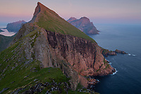 Breiflogtind mountain peak rises from the sea into the summer twilight, Moskenesøy, Lofoten Islands, Norway