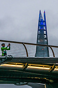 A man takes a picture on the Millennium Bridge as the Shard is lit up in blue in support of the National Health Service (NHS), as the capital is set to reopen after the lockdown due to the coronavirus outbreak, in London, Saturday, July 4, 2020. Sunday marks the 72nd anniversary of the formation of the National Health Service (NHS). The UK has hailed its NHS for the work they have done during the Covid-19 pandemic. (VXP Photo/ Erica Dezonne)