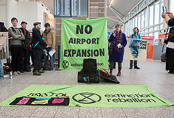© Licensed to London News Pictures. 18/01/2019. Bristol Airport, Lulsgate, North Somerset, UK. MOLLY SCOTT CATO, Green MEP for south west England, speaks at an Extinction Rebellion protest in the departure hall at Bristol Airport, to protest against plans to expand the airport and against frequent flying which they say causes both pollution and climate change. Molly Scott Cato, Green MEP for south west England, spoke in support. Photo credit: Simon Chapman/LNP