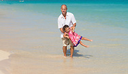 playing on beach father daughter