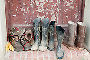 Work boots are lined up in front on a well worn door on a small farm in Italy.