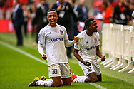AFC Flyde forward Alex Reid (30) and AFC Flyde defender Timi Odusina 18) slide towards fans to celebrate winning  the FA Trophy final match between AFC Flyde and Leyton Orient at Wembley Stadium on 19 May 2019.