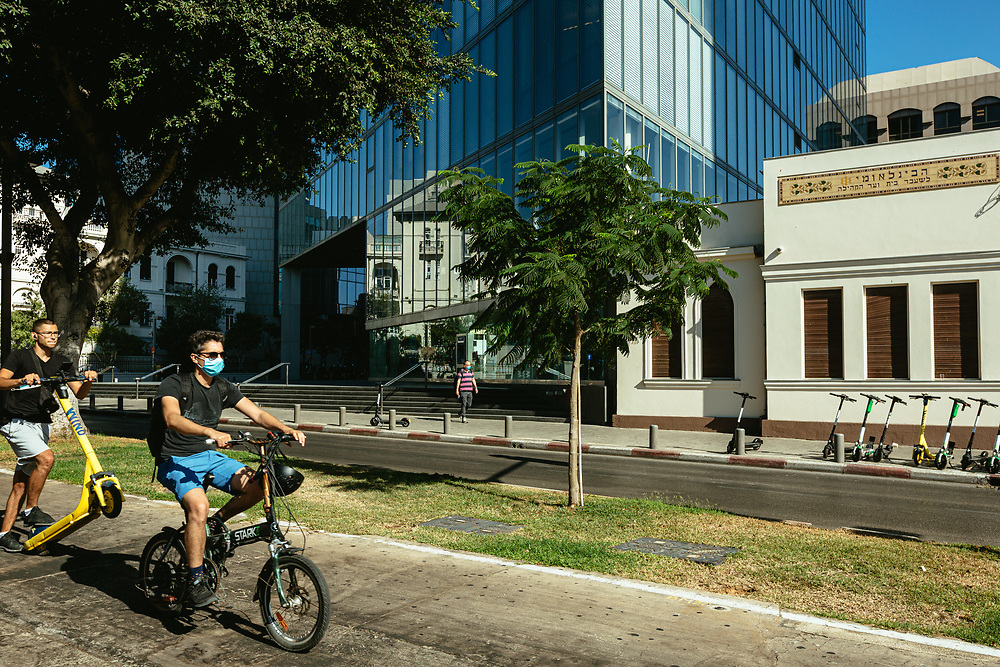 Cyclists and electric scooter riders are seen driving along Sderot Rothschild (Rothschild Boulevard), a mostly a tree-lined boulevard with lanes for pedestrians and cyclists, playgrounds for children, coffee shops and kiosks in central Tel Aviv, Israel, on August 19, 2020.