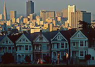 Victorian row houses line the street in front of Alamo Park with the city of San Francisco skyline in the background.