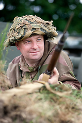 """A re-enactor from the Northern World War Two Association Living History group portrays a member of the British 5th Battalion, East Yorkshires, 50th Division complete with classic Brodie """"tin helmet"""" Lee Enfield Rifle and fixed Bayonet. SPAM 1940's Weekend Heckmonwyke near Wakefield 10 July 2010 .Images © Paul David Drabble."""