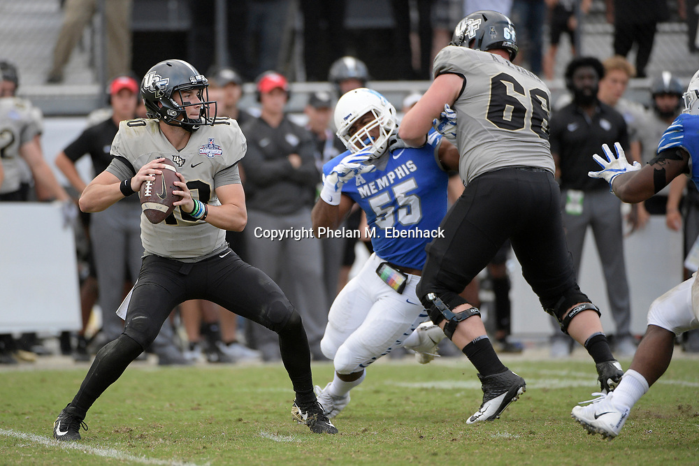 Central Florida quarterback McKenzie Milton (10) sets up to pass as offensive lineman Aaron Evans (66) blocks Memphis linebacker Bryce Huff (55) during the second half of the American Athletic Conference championship NCAA college football game Saturday, Dec. 2, 2017, in Orlando, Fla. Central Florida won 62-55. (Photo by Phelan M. Ebenhack)