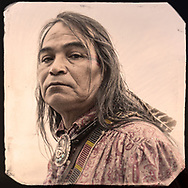Handsome native Indian man with a feather in his long graying hair wearing beaded suspenders, a red paisley shirt and a silver and turquoise bolo tie.