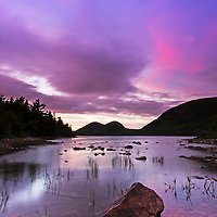 Dramatic cloudscape at Jordan Pond in the early fall as seen at sunset. This beautiful pond is in the heart of Acadia National Park on Mount Desert Island and one of the best photo location for seascape photography. The shore line and rocks in the foreground provide interesting elements for pleasing  compositions while the South and North Bubbles in the background are iconic photo subjects. <br />
