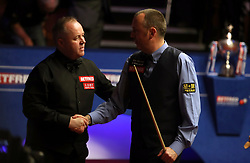 Mark Williams (right) and John Higgins shake hands during day seventeen of the 2018 Betfred World Championship at The Crucible, Sheffield.
