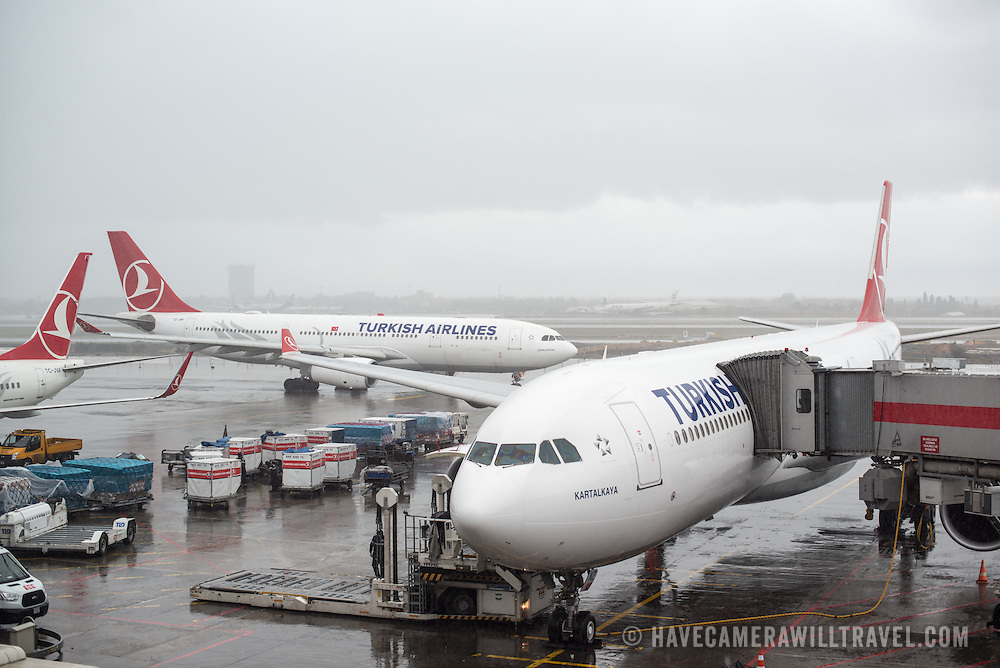Three Turkish Airlines passenger planes at Istanbul Atatürk Airport (aiport code IST). Two are docked at gates, with a third taxiing to the runway for takeoff.