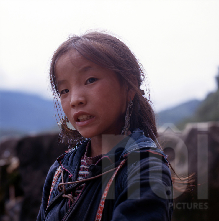 a young H'mong girl in traditional outfit outside Sapa, Vietnam.