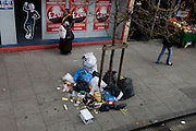 Londoners walk past mess of litter and rubbish torn apart on a south London street in the borough of Lambeth.