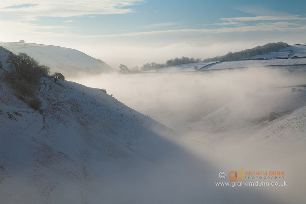 An atmospheric morning as the rising sun illuminates mist in a snow-covered Cressbrook Dale. A winter landscape scene in the Derbyshire Peak District. White Peak, England, UK.