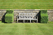 A Medieval style timber seat flanked by buttresses of clipped box (Buxus sempervirens) against a Cotswold stone wall in an English country garden.<br /> <br /> Date taken: 16 June 2010.