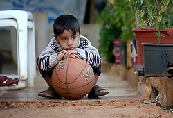 A Syrian refugee child plays with a ball in a settlement camp where he lives amongst an olive grove in Koura, near Tripoli, Lebanon.