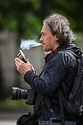 Press photographer from Poland, Wiktor Szymanowicz is seen taking a break during a protest against Viktor Lukashenko regime of Belarus outside Westminster Palace, Houses of Parliament in London on Sunday, Aug 8, 2021. (VX Photo/ Vudi Xhymshiti)
