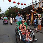 Tourists are driven around town on a Cyclo, Hoi An, Vietnam. Hoi An is an ancient town and an exceptionally well-preserved example of a South-East Asian trading port dating from the 15th century. Hoi An is now a major tourist attraction because of its history. Hoi An, Vietnam. 5th March 2012. Photo Tim Clayton