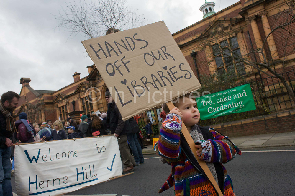 A young person holds a placard demanding Lambeth council keeps their hands of public libraries. Faced with the closure of its beloved local library, the people of Herne Hill, Lambeth, south London hold a demonstration outside the Edwardian library. Lambeth council plan to close the facility used by the community as part of austerity cuts, saying they will convert the building into a gym and privately-owned gentrified businesses - rather than a much-loved reading and learning resource. £12,600 was donated by the American philanthropist Andrew Carnegie to help build the library which opened in 1906. It is a fine example of Edwardian civic architecture, built with red Flettan bricks and terracotta, listed as Grade II in 1981.