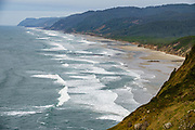 Pacific Ocean waves roll onto Hobbit Beach, seen from a trail on the headland within Heceta Head Lighthouse State Scenic Viewpoint, on the Oregon coast, USA. Here, the Siuslaw Indians traditionally hunted sea lions and gathered sea bird eggs from offshore rocks. While seeking to extend Spanish hegemony in the late 1700s, Spanish explorer Bruno de Heceta mapped the mouth of the Columbia River and much more along the Pacific Northwest coast; and in 1862, the US Coast Survey named Heceta Head in his honor. Heceta Head is found halfway between Yachats and Florence (2.1 miles south of Carl Washburne State Park). From the large parking lot, walk 1 mile round trip to the Lighthouse. (Heceta Head Lighthouse State Scenic Viewpoint was created in the 1990s by combining Heceta Head State Park with the former Devils Elbow State Park at the scenic cove at the mouth of Cape Creek.)