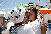 Woman being blessed by a Bahiana outside the church. Often the lines between Candomble and Catholicism are blurred. This is especially true with the Sao Lazaro event in late January in Salvador, Bahia, Brazil, the city which is known as the home of Candomble. Sao Lazaro represents healing and the sick.