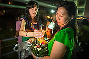 28 NOVEMBER 2012 - BANGKOK, THAILAND: Women light the candles and incense on their krathong before placing them in the Chao Phraya River on Loy Krathong at Wat Yannawa in Bangkok. Loy Krathong takes place on the evening of the full moon of the 12th month in the traditional Thai lunar calendar. In the western calendar this usually falls in November. Loy means 'to float', while krathong refers to the usually lotus-shaped container which floats on the water. Traditional krathongs are made of the layers of the trunk of a banana tree or a spider lily plant. Now, many people use krathongs of baked bread which disintegrate in the water and feed the fish. A krathong is decorated with elaborately folded banana leaves, incense sticks, and a candle. A small coin is sometimes included as an offering to the river spirits. On the night of the full moon, Thais launch their krathong on a river, canal or a pond, making a wish as they do so.    PHOTO BY JACK KURTZ
