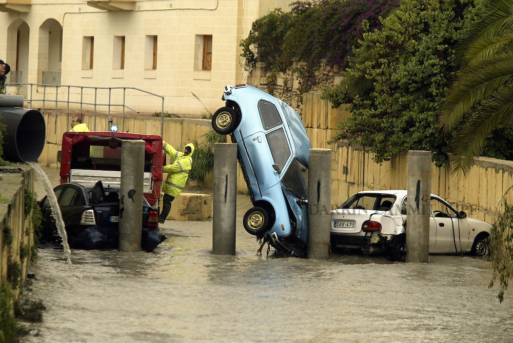 Civil Protection officers attempt to clear away cars which were swept away by flood waters in the town of Birkirkara, outside Valletta, November 6, 2002.  Heavy rainfall caused widespread flooding and damage throughout the Maltese islands, though no serious injuries were reported...MALTA OUT..REUTERS/Darrin Zammit Lupi