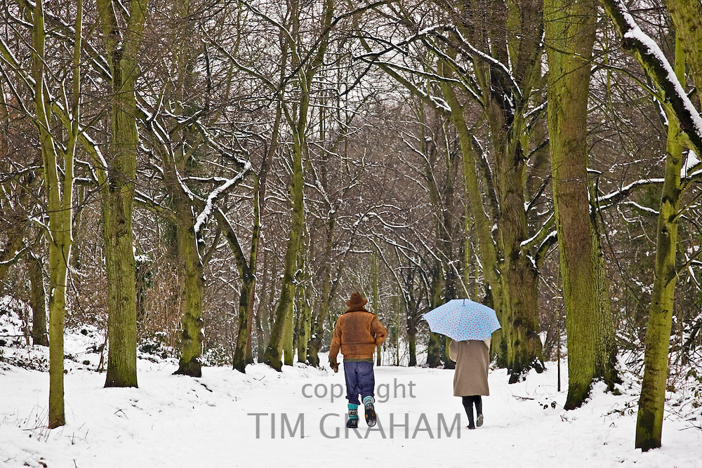 Winter scene as couple walk together across snow-covered Hampstead Heath, North London, United Kingdom