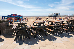 © Licensed to London News Pictures; 25/05/2020; Weston-super-Mare, UK. Table stacked on the promenade as some attractions are still closed during the coronavirus pandemic. General views today of crowds on Weston's beach and promenade on a spring bank holiday Monday. Weston General Hospital has said it is temporarily closed to new admissions including for A&E due to the high number of Covid-19 coronavirus patients it is caring for in the hospital. Last week there was concern in Weston-super-Mare about the high number of visitors to the beach and seafront during the warm weather. Photo credit: Simon Chapman/LNP.