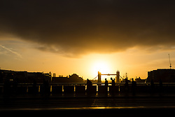 © Licensed to London News Pictures. 17/10/2014. London, UK. Commuters cross London Bridge and black clouds soon appear just after an orange sunrise behind Tower Bridge in London this morning. Photo credit : Vickie Flores/LNP