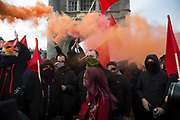 Anarchists gather as a black bloc letting off smoke bombs for the Fuck Parade to party and protest at the class and wealth divide between rich and poor and the gentrification of London, the demonstration was organised by anarchist group Class War on May 1st 2016 in London, United Kingdom. The parade is now part of the May Day activism calendar as dissatisfaction about the establishment, the police and the inadequacy of the press is highlighted. Here the group shows its anger, blocking traffic on Tower Bridge and shouting slogans.