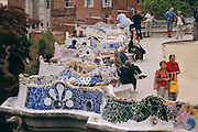 Visitors relax on undulating mosaic benches on an overlook in Parc Guell, architect Antonin Gaudi's imaginative park in Barcelona, Spain.